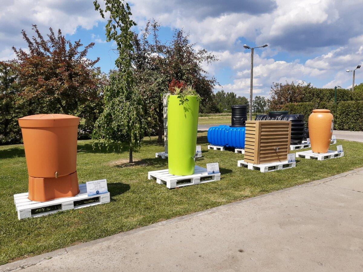 Na zdjęciu zbiorniki na deszczówkę stojące na tle drzew na białych paletach , od lewej brązowy okrągły, następnie zielony , obok brazowy prostokatny, następnie brązowa amfora, w tle niebieski i czarny podziemny zbiornik